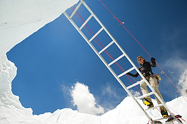 A climber on Everest makes her way across a crevasse using a temporary ladder, Khumbu Region, Himalayas, Nepal, Asia