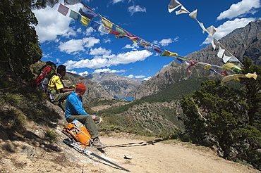 Prayer flags mark a high point in the trail where trekkers are rewarded with their first glimpse of Phoksundo Lake, Dolpa Region, Himalayas, Nepal, Asia