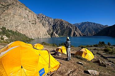 A trekker looks out at the turquoise blue Phoksundo Lake, Dolpa Region, Nepal, Asia