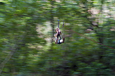 A girl clings on and laughs with delight on a zip line, Nepal, Asia