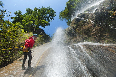 A man pauses to smile for the camera while canyoning in a waterfall, Nepal, Asia