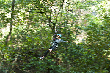 A girl holds her arms out while on a zip line, Nepal, Asia