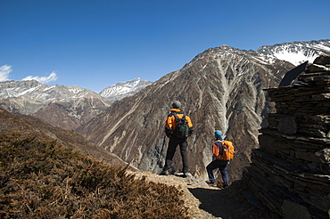 Trekkers stop by a chorten in the Tsum Valley near Mu Gompa, Nepal, Asia