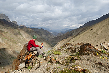 Stopping to savour the views from the top of the Konze La, at 4900m, during the Hidden Valleys trek in Ladakh, a remote Himalayan region, India, Asia