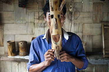 A young man holds a mask made from bamboo to his face, Assam, India, Asia