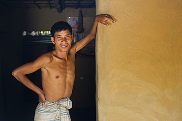 A man stands in the entrance of his mud walled house near Kaptai Lake, Chittagong Hill Tracts, Bangladesh, Asia