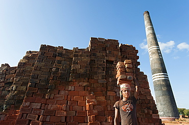 A young man carries a pile of bricks on his head at a brick factory, Chittagong Hill Tracts, Bangladesh, Asia
