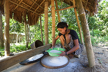 A woman mills grain into flour using a tradiional mill, Chittagong Hill Tracts, Bangladesh, Asia