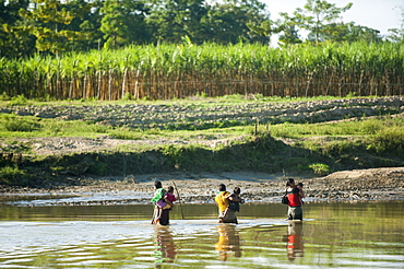 Women cross a river carrying their children in their arms, Chittagong Hill Tracts, Bangladesh, Asia