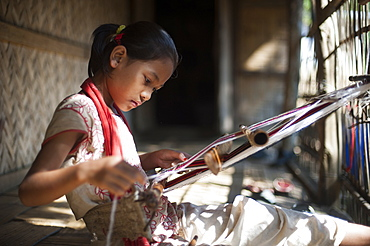 A little girl learns the skill of weaving on a handloom, Chittagong Hill Tracts, Bangladesh, Asia