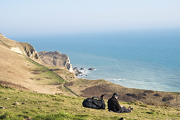 A man takes a break from a coastal walk near Lulworth Cove in Dorset, Jurassic Coast, UNESCO World Heritage Site, England, United Kingdom, Europe