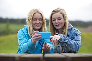 Girls reading a smartphone, England, United Kingdom, Europe