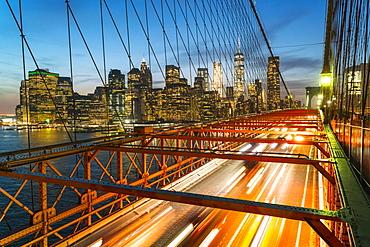 Rush hour traffic at night on Brooklyn Bridge and Manhattan skyline beyond, New York City, United States of America, North America