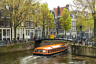 Canal boat passing under a bridge on Brouwersgracht, Amsterdam, Netherlands, Europe