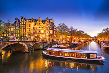 Canal scene with tour boat at dusk, Amsterdam, Netherlands, Europe