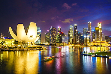 The lotus flower shaped ArtScience Museum overlooking Marina Bay with the city skyline beyond illuminated at night, Singapore, Southeast Asia, Asia