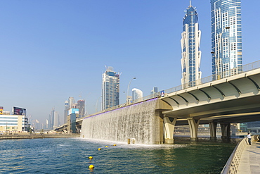 Dubai Water Canal Waterfall Bridge, the waterfall parts to allow boats to pass under, Business Bay, Dubai, United Arab Emirates, Middle East
