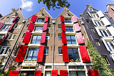 Red shutters on traditional Dutch style building, Amsterdam, North Holland, The Netherlands, Europe