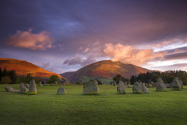 Castlerigg Stone Circle in autumn at sunrise with Blencathra bathed in dramatic dawn light, Lake District National Park, Cumbria, England, United Kingdom, Europe