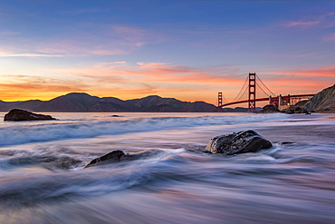 Soft flowing water reflects the beautiful colors in the sky as the sun sets near the Golden Gate Bridge, San Francisco, California, United States of America, North America