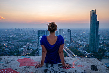 A single woman watching sun set over city skyline at dusk, Bangkok, Thailand, Southeast Asia, Asia