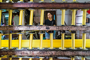 A silk weaver creates a bolt of gold thread at a traditional workshop in Bangkok, Thailand, Southeast Asia, Asia