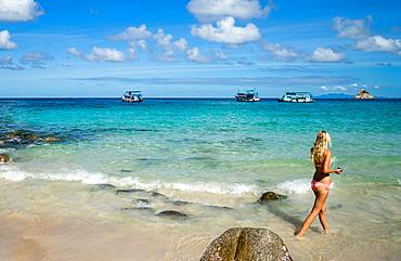 A woman in a bikini walks along a beach on Koh Tao, Thailand, Southeast Asia, Asia
