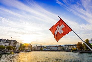 Swiss flag at sunset, River Rhone, Geneva, Switzerland, Europe