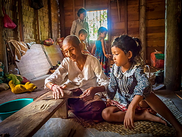 Old woman making incense as child watches, village near Siem Reap, Cambodia, Indochina, Southeast Asia, Asia