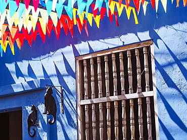 Colorful flags and a blue building with a cat sign, Getsemani barrio, Cartagena, Colombia, South America