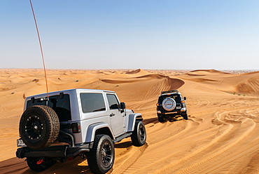 Off road vehicles on sand dunes near Dubai in the United Arab Emirates, Middle East