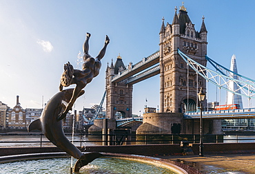 Juxtaposition of David Wynne's Girl With A Dolphin statue near Tower Bridge and Victorian engineering on the River Thames, London, England, United Kingdom, Europe
