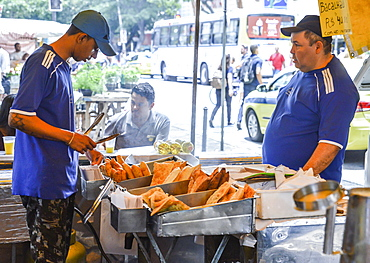 Market workers prepare a fried dish, known as pastel which can be served with cheese or meat, Rio de Janeiro, Brazil, South America