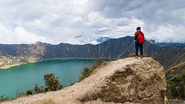 A woman started at Quilotoa, a water-filled caldera and the most western volcano in the Ecuadorian Andes, Ecuador, South America