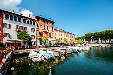 Boats on marina with tourists at cafes and restaurants at Desenzano del Garda, Lake Garda, Lombardy, Italian Lakes, Italy, Europe
