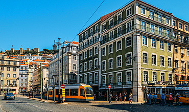 Traditional trams at Praca da Figueira with Castelo Sao Jorge on the far left, Lisbon, Portugal, Europe