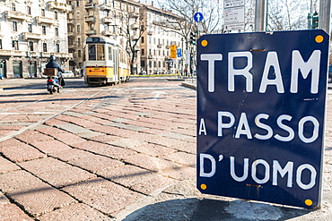 An old sign in Italian that says Trams go to Duomo, with a traditional Milanese tram in the background, Milan, Lombardy, Italy, Europe
