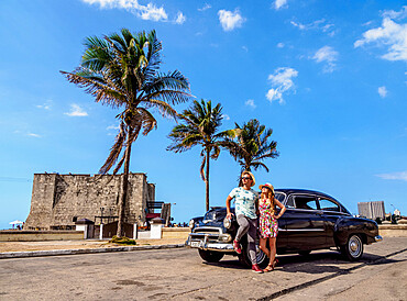 Cuban Couple with Vintage Chevrolet Car, Tower of la Chorrera in the background, Havana, La Habana Province, Cuba, West Indies, Caribbean, Central America