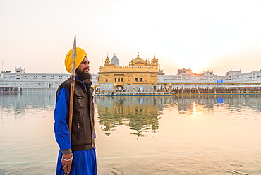 Guard standing by tank, the Golden Temple, Amritsar, Punjab, India, Asia