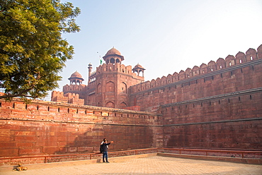 A couple take a selfie while a dog sunbathes at The Red Fort, UNESCO World Heritage Site, Old Delhi, India, Asia