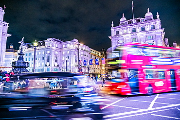 A bus and taxi zoom round Piccadilly Circus, London, England, United Kingdom, Europe