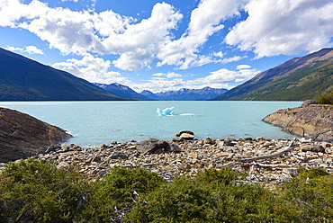 A single iceberg floating near the shore in Lago Argentino near Perito Moreno Glacier, with mountains in the background, Los Glaciares National Park, UNESCO World Heritage Site, Patagonia, Argentina, South America