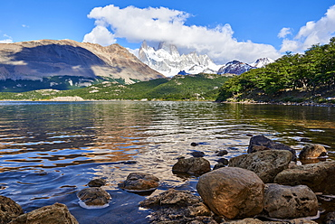 Wide angle shot of Capri Lagoon featuring Monte Fitz Roy in the background and rocks in the foreground, Patagonia, Argentina, South America