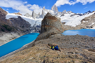 A couple in mountain gear rests on rocks with view to Lago de los Tres and Mount Fitz Roy, Patagonia, Argentina, South America
