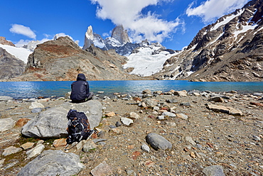 A lone figure in mountain gear rests on rocks with view to Lago de los Tres and Mount Fitz Roy, their backpack on the ground, Patagonia, Argentina, South America