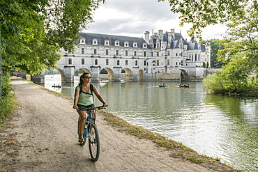 Girl cycling with Chenonceau castle on the background, UNESCO World Heritage Site, Chenonceaux, Indre-et-Loire, Centre, France, Europe