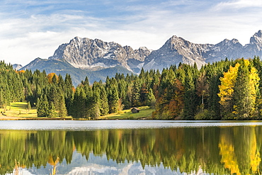 Lodge, forest and Karwendel Alps reflected in the waters of Gerold Lake, Krun, Upper Bavaria, Bavaria, Germany.