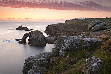 A colourful sunset overlooking the islands of Enys Dodnan and the Armed Knight at Lands End, Cornwall, England, United Kingdom, Europe