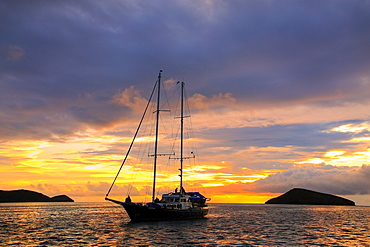 Silhouetted tourist sailboat at sunrise anchored near Chinese Hat island in Galapagos National Park, Ecuador, South America