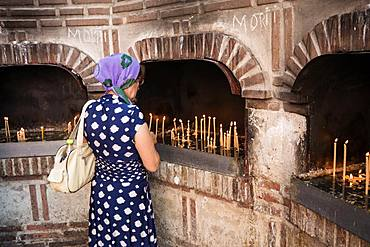 A female worshiper lights a candle outside the Biserica Sfantul Anton in Bucharest, Romania, Europe